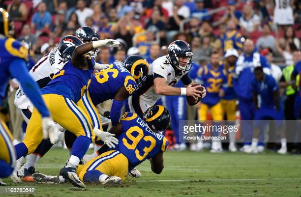 Quarterback Kevin Hogan of the Denver Broncos is sacked by defensive tackle Marquise Copeland and linebacker Landis Durham of the Los Angeles Rams...