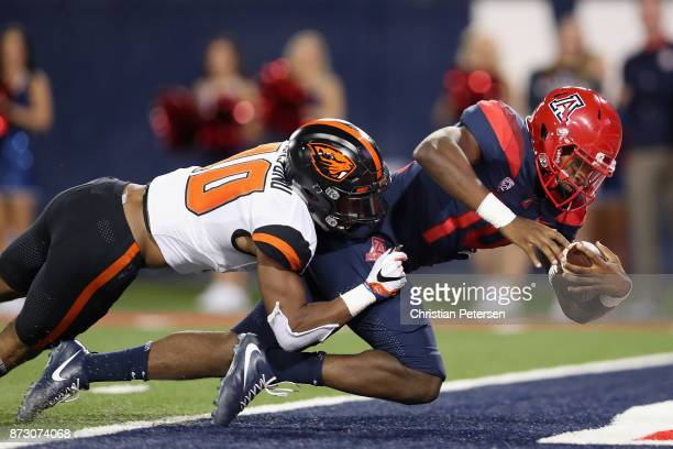 Quarterback Khalil Tate of the Arizona Wildcats dives into the end zone to score on a 19 yard rushing touchdown against safety Omar Hicks-Onu of the...