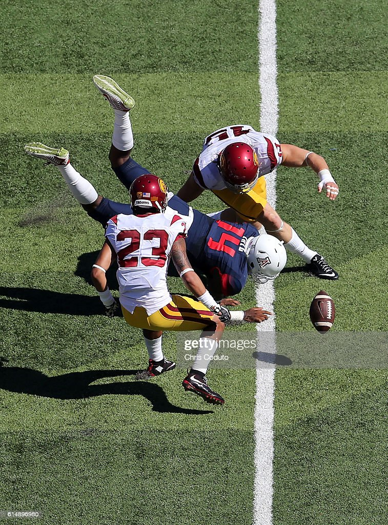 Quarterback Khalil Tate #14 of the Arizona Wildcats fumbles after being hit by defensive end Porter Gustin #45 and defensive back Jonathan Lockett #23 of the USC Trojans during the second quarter of the college football game at Arizona Stadium on October 15, 2016 in Tucson, Arizona.