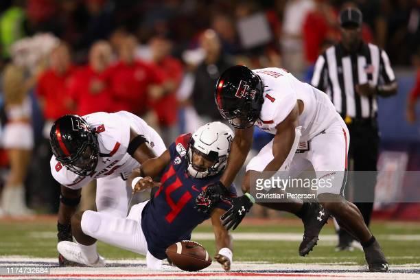 Quarterback Khalil Tate of the Arizona Wildcats fumbles the football as linebackers Riko Jeffers and Jordyn Brooks of the Texas Tech Red Raiders...