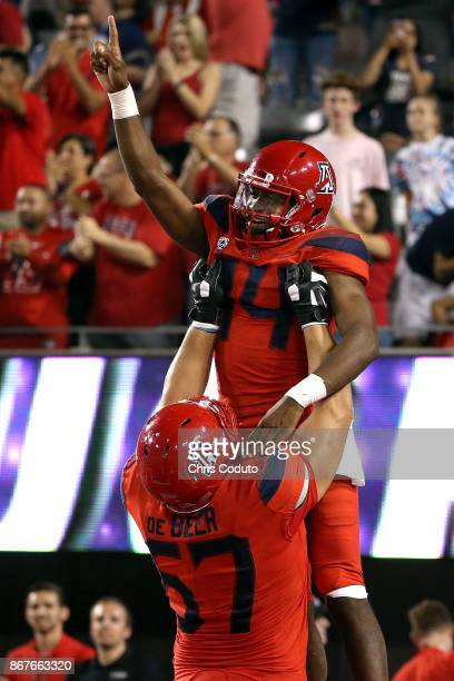 Quarterback Khalil Tate of the Arizona Wildcats reacts with offensive lineman Gerhard de Beer after scoring a second half touchdown during the...