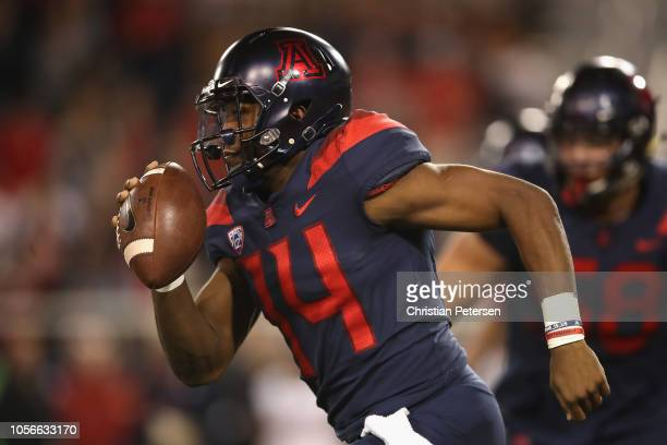 Quarterback Khalil Tate of the Arizona Wildcats scrambles with the football against the Colorado Buffaloes during the second half of the college...