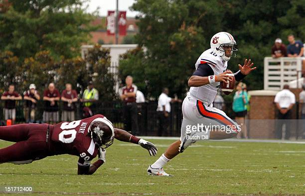Quarterback Kiehl Frazier of the Auburn Tigers scrambles away from defensive lineman Denico Autry of the Mississippi State Bulldogs in the first...