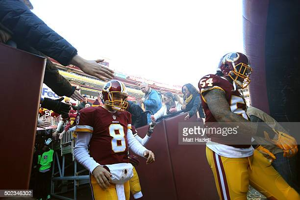 Quarterback Kirk Cousins and linebacker Mason Foster of the Washington Redskins walk on the field before a game against the Buffalo Bills at...