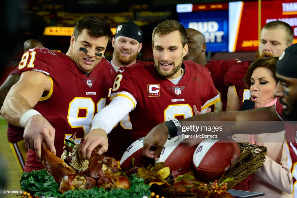 Quarterback Kirk Cousins #8 and outside linebacker Ryan Kerrigan #91 of the Washington Redskins eat turkey after the Redskins defeated the New York Giants 20-10 at FedExField on November 23, 2017 in Landover, Maryland.