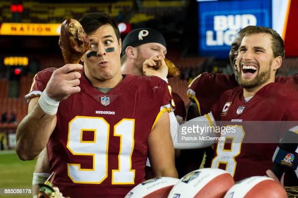 Quarterback Kirk Cousins and outside linebacker Ryan Kerrigan of the Washington Redskins eat turkey after the Redskins defeated the New York Giants...