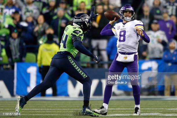 Quarterback Kirk Cousins of the Minnesota Vikings drops back to pass over the defense of defensive end Ezekiel Ansah of the Seattle Seahawks during...