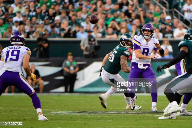 Quarterback Kirk Cousins of the Minnesota Vikings throws a pass to teammate wide receiver Adam Thielen against defensive end Chris Long of the...