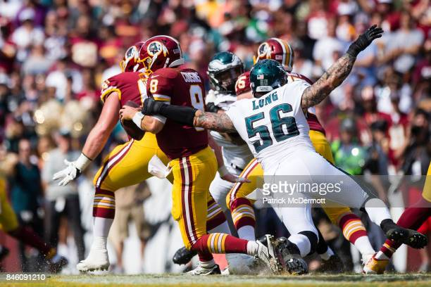 Quarterback Kirk Cousins of the Washington Redskins avoids the tackle of Chris Long of the Philadelphia Eagles in the second half at FedExField on...