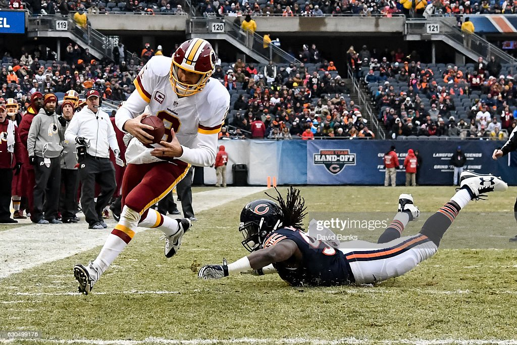 Quarterback Kirk Cousins #8 of the Washington Redskins carries the football into the endzone past Pernell McPhee #92 of the Chicago Bears for a Redskins touchdown in the second quarter at Soldier Field on December 24, 2016 in Chicago, Illinois.