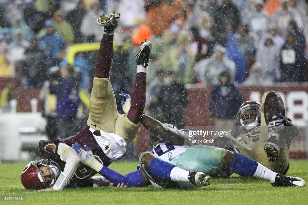 Quarterback Kirk Cousins #8 of the Washington Redskins gets hit by defensive end Demarcus Lawrence #90 of the Dallas Cowboys during the fourth quarter at FedEx Field on October 29, 2017 in Landover, Maryland.