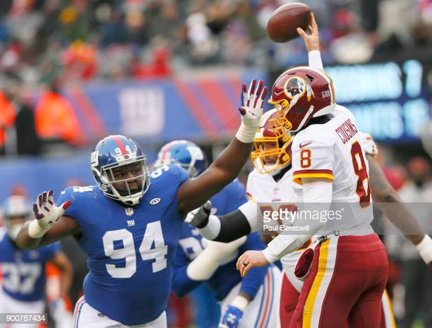 Quarterback Kirk Cousins of the Washington Redskins has to throw the ball away as he is under pressure by Dalvin Tomlinson of the New York Giants in...