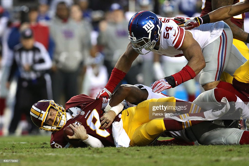 Quarterback Kirk Cousins #8 of the Washington Redskins is sacked by defensive end Olivier Vernon #54 and strong safety Landon Collins #21 of the New York Giants in the first quarter at FedExField on January 1, 2017 in Landover, Maryland.