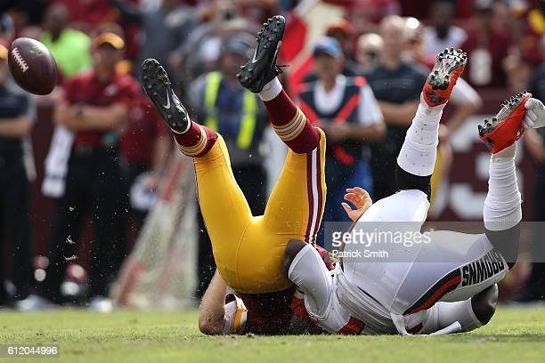 Quarterback Kirk Cousins of the Washington Redskins is tackled by defensive end Cam Johnson of the Cleveland Browns in the third quarter at...