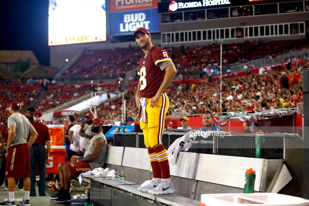 Quarterback Kirk Cousins #8 of the Washington Redskins stands on a bench and looks on from the sidelines during the second quarter of an NFL preseason football game against the Tampa Bay Buccaneers on August 31, 2017 at Raymond James Stadium in Tampa, Florida.