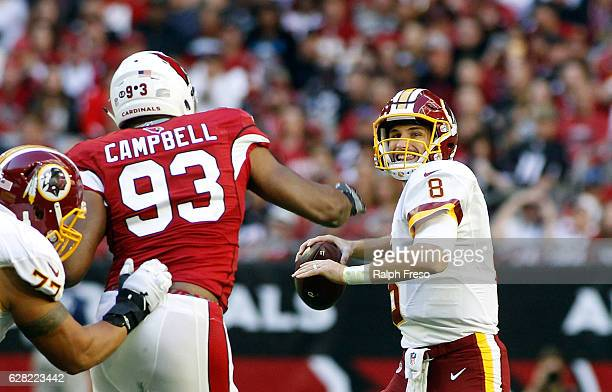 Quarterback Kurk Cousins of the Washington Redskins looks to pass as he is pressured by Calais Campbell of the Arizona Cardinals during the first...