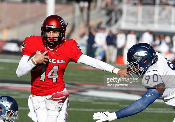 UNLV quarterback Kurt Palandech attempts to run around Nevada defensive end Malik Reed during a game against the Nevada Wolfpack on November 26 2016...