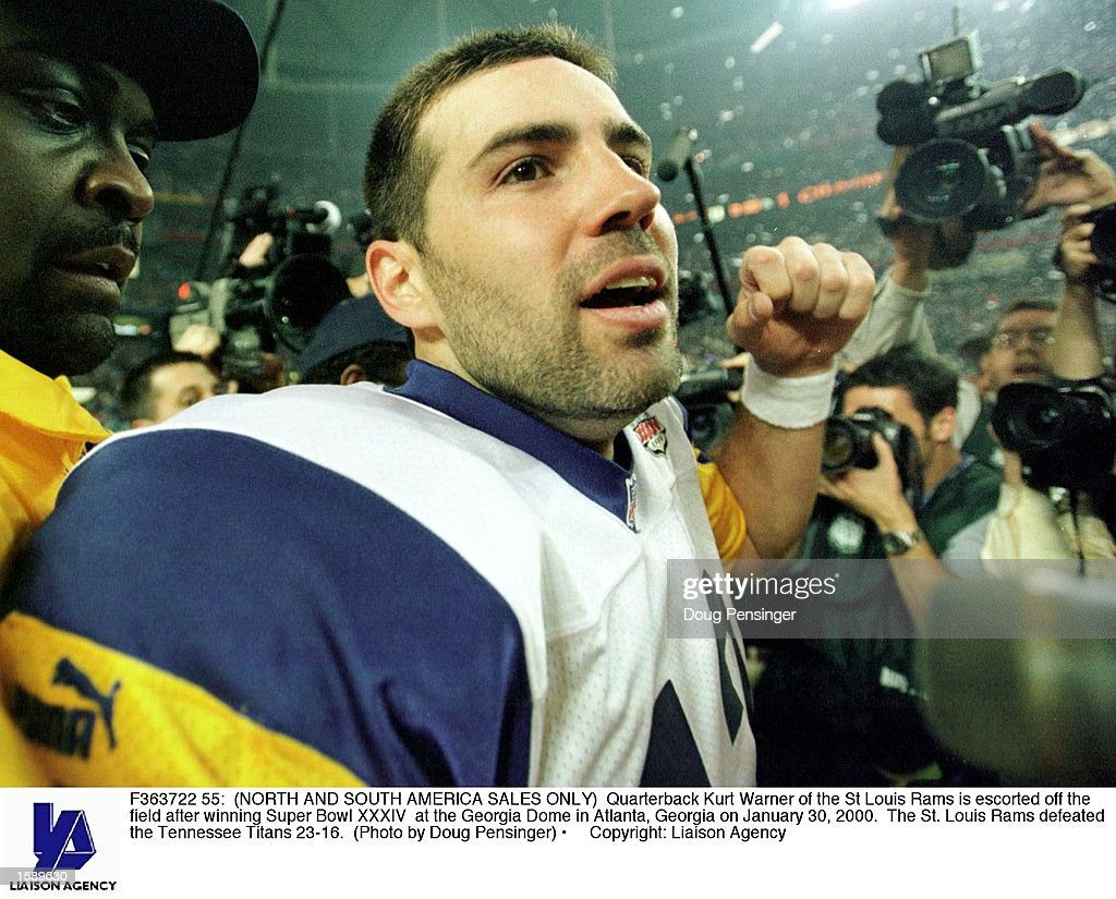 Quarterback Kurt Warner of the St Louis Rams is escorted off the field after winning Super Bowl XXXIV at the Georgia Dome in Atlanta, Georgia on January 30, 2000. The St. Louis Rams defeated the Tennessee Titans 23-16.