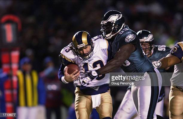 Quarterback Kurt Warner of the St Louis Rams is sacked by defensive end Hugh Douglas of the Philadelphia Eagles during the NFL game on December 1...