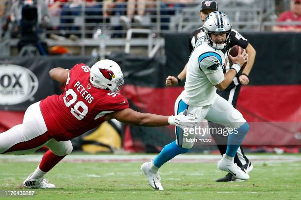 Quarterback Kyle Allen of the Carolina Panthers eludes the tackle of Corey Peters of the Arizona Cardinals during the second half of the NFL football...