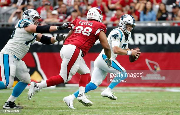 Quarterback Kyle Allen of the Carolina Panthers scrambles away from Corey Peters of the Arizona Cardinals during the second half of the NFL football...