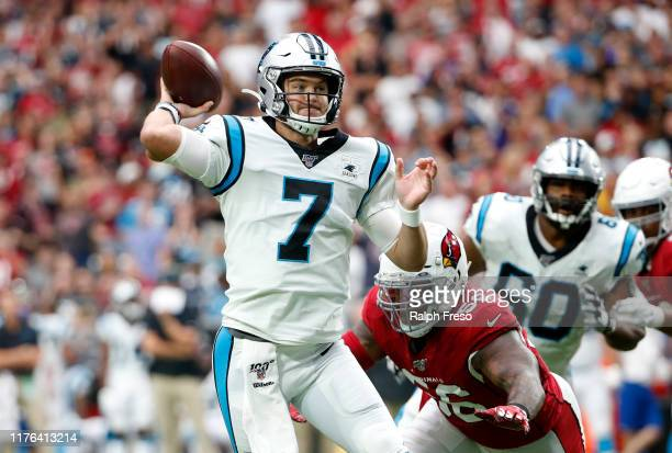 Quarterback Kyle Allen of the Carolina Panthers throws a touchdown pass as he is pressured by Terrell Suggs of of the Arizona Cardinals during the...