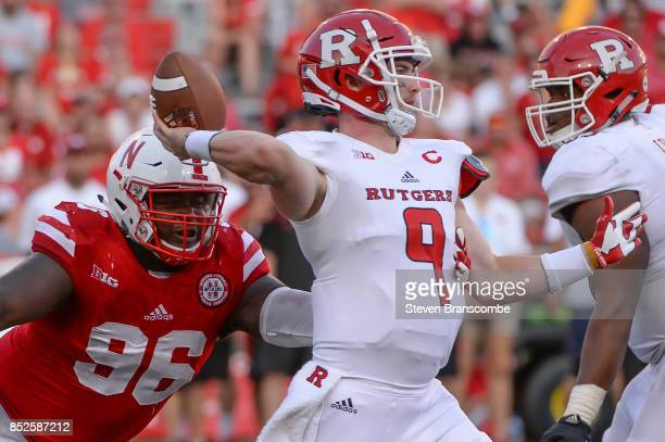 Quarterback Kyle Bolin of the Rutgers Scarlet Knights attempts a pass ahead of the rush from defensive lineman Carlos Davis of the Nebraska...