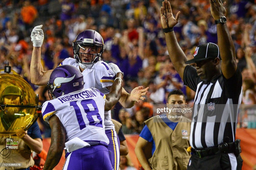 Quarterback Kyle Sloter #1 and wide receiver Korey Robertson #18 of the Minnesota Vikings celebrate a fourth quarter touchdown on a quarterback keeper against the Denver Broncos during an NFL preseason game at Broncos Stadium at Mile High on August 11, 2018 in Denver, Colorado.