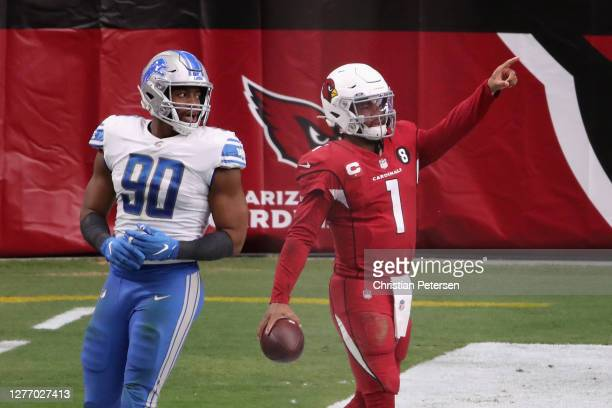 Quarterback Kyler Murray of the Arizona Cardinals celebrates after scoring on a 1-yard rushing touchdown against defensive end Trey Flowers of the...