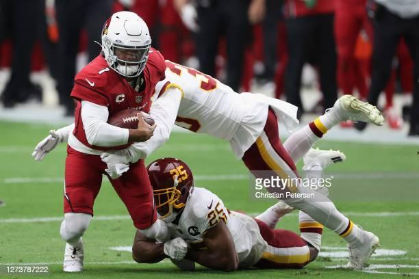 Quarterback Kyler Murray of the Arizona Cardinals runs with the football against free safety Troy Apke and cornerback Fabian Moreau of the Washington...