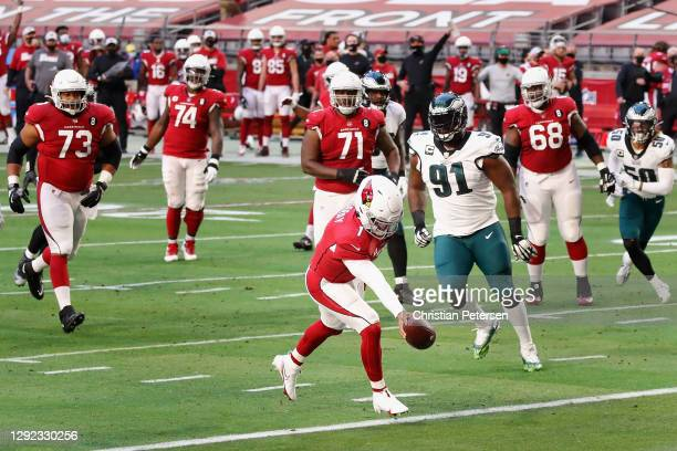 Quarterback Kyler Murray of the Arizona Cardinals scores an eight-yard rushing touchdown past defensive tackle Fletcher Cox of the Philadelphia...