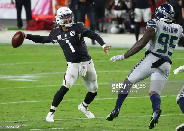 Quarterback Kyler Murray of the Arizona Cardinals throws the ball away on fourth and three as defensive end Benson Mayowa of the Seattle Seahawks...