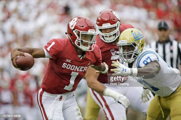 Quarterback Kyler Murray of the Oklahoma Sooners scrambles away from defensive lineman Odua Isibor of the UCLA Bruins at Gaylord Family Oklahoma...