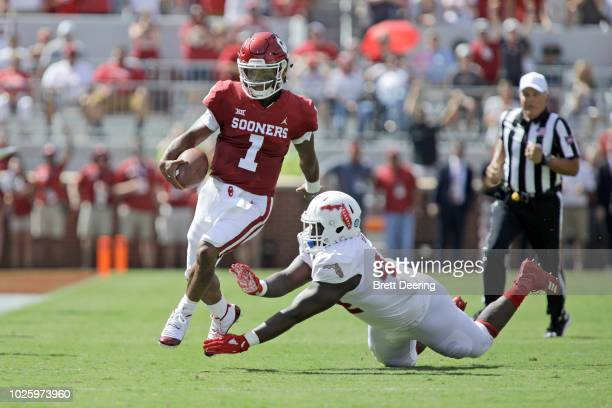 Quarterback Kyler Murray of the Oklahoma Sooners steps away from defensive tackle William Davis of the Florida Atlantic Owls at Gaylord Family...
