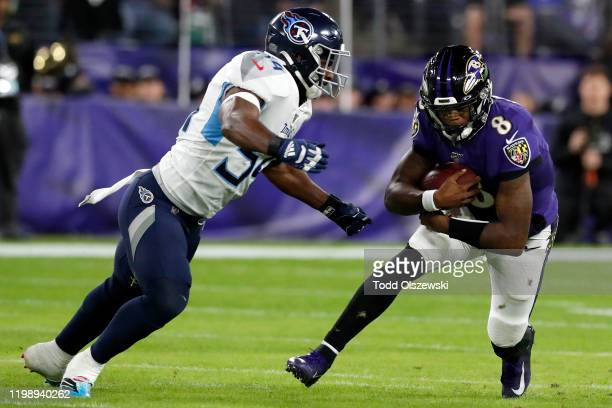 Quarterback Lamar Jackson of the Baltimore Ravens carries the ball against Rashaan Evans of the Tennessee Titans during the AFC Divisional Playoff...