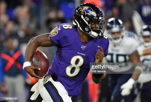 Quarterback Lamar Jackson of the Baltimore Ravens carries the ball against the defense of the Tennessee Titans during the AFC Divisional Playoff game...