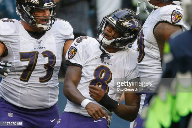 Quarterback Lamar Jackson of the Baltimore Ravens celebrates with Marshal Yanda after scoring a touchdown in the third quarter against the Seattle...