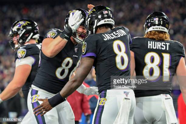 Quarterback Lamar Jackson of the Baltimore Ravens celebrates with teammates after scoring a first quarter touchdown against the New England Patriots...
