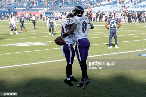 Quarterback Lamar Jackson of the Baltimore Ravens celebrates with teammate running back Justice Hill following a 48-yard touchdown run by Jackson...