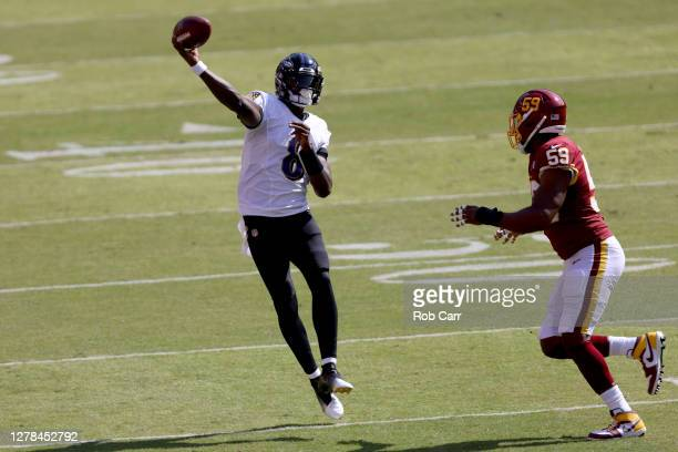 Quarterback Lamar Jackson of the Baltimore Ravens gets off a pass while being pressured by Nate Orchard of the Washington Football Team in the first...