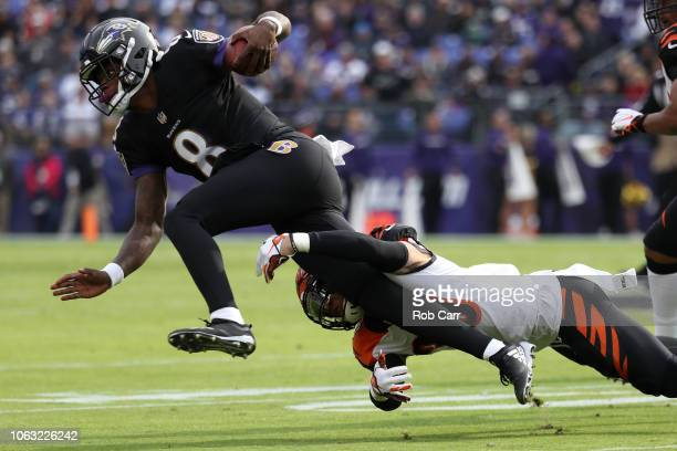 Quarterback Lamar Jackson of the Baltimore Ravens is tackled as he carries the ball by free safety Jessie Bates of the Cincinnati Bengals in the...