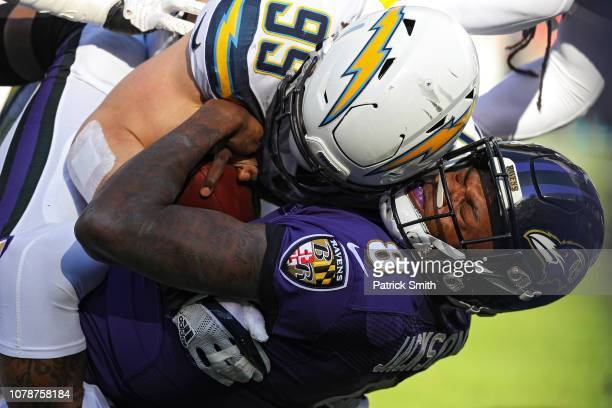 Quarterback Lamar Jackson of the Baltimore Ravens is tackled by defensive tackle Joey Bosa of the Los Angeles Chargers in the first quarter during...