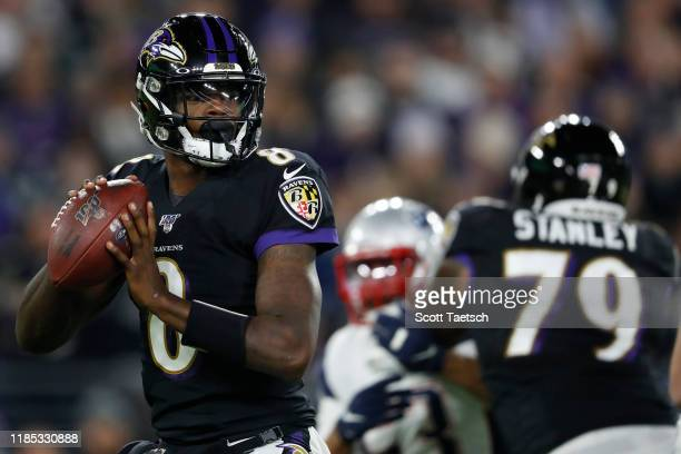 Quarterback Lamar Jackson of the Baltimore Ravens looks to pass against the New England Patriots during the first quarter at MT Bank Stadium on...