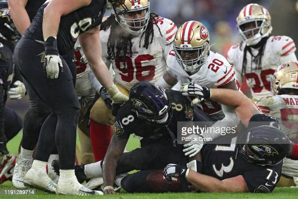 Quarterback Lamar Jackson of the Baltimore Ravens rushes for a first down against the San Francisco 49ers during the fourth quarter at MT Bank...