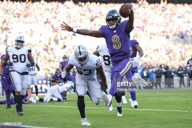 Quarterback Lamar Jackson of the Baltimore Ravens rushes for a touchdown during the third quarter against the Oakland Raiders at MT Bank Stadium on...