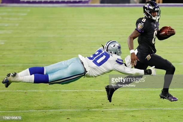 Quarterback Lamar Jackson of the Baltimore Ravens rushes past defensive end DeMarcus Lawrence of the Dallas Cowboys during the fourth quarter at M&T...