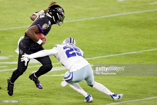Quarterback Lamar Jackson of the Baltimore Ravens rushes past free safety Xavier Woods of the Dallas Cowboys during the first half at M&T Bank...