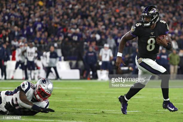 Quarterback Lamar Jackson of the Baltimore Ravens scores a first quarter touchdown against the New England Patriots at MT Bank Stadium on November 3...