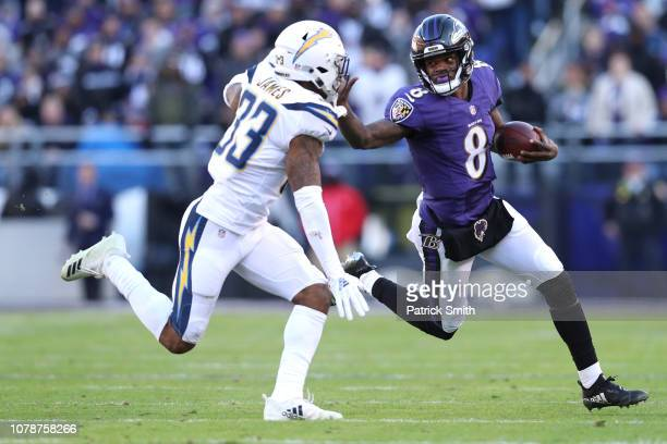 Quarterback Lamar Jackson of the Baltimore Ravens stiff arms free safety Derwin James of the Los Angeles Chargers in the second half during the AFC...