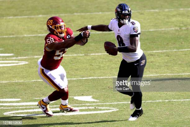 Quarterback Lamar Jackson of the Baltimore Ravens stiff arms Nate Orchard of the Washington Football Team to avoid a sack in the second half at...